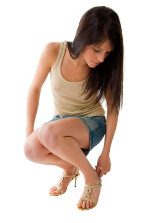 beautiful girl wearing miniskirt and undershirt adapts her sandals. Girl isolated in white background