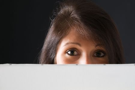 A beautiful and attractive girl holding a billboard. Ready to add your own text. Copy-space on a sign or poster. Young girl holding a sign, advertisement or poster. The concept of this picture is: copy-space on a white board or advertising.