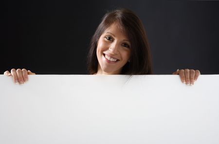 A beautiful and attractive girl holding a billboard. Ready to add your own text. Copy-space on a sign or poster. Young girl holding a sign, advertisement or poster. The concept of this picture is: copy-space on a white board or advertising. photo