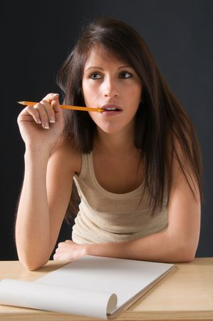 Portrait of a beautiful Isolated  teenager  student. An attractive young student posing at her desk. Picture of a pretty girl isolated on a dark background. photo