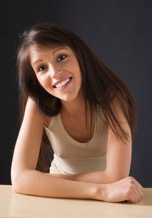 Portrait of a beautiful isolated young female student. Smiling young student posing at her desk. Close-up of a sexy, sensual young woman staring at the camera. Stock Photo