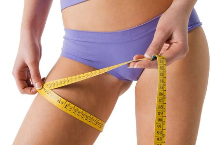 Girl measuring her thigh checking the result of diet. Stock Photo