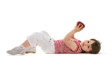 Pretty child lying on the floor with a red apple in hand