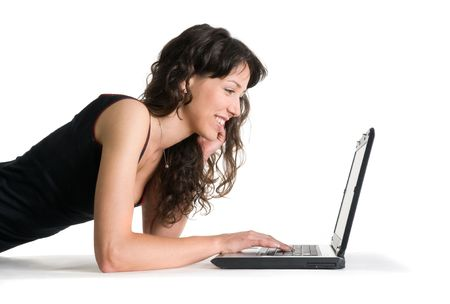 Smiling girl works with the laptop lying on the floor Stock Photo