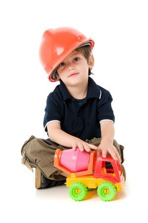 Child  with hard hat playng sitting on the floor Stock Photo