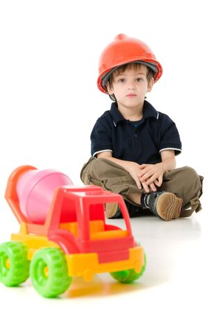 Child  with hard hat sitting on the floor