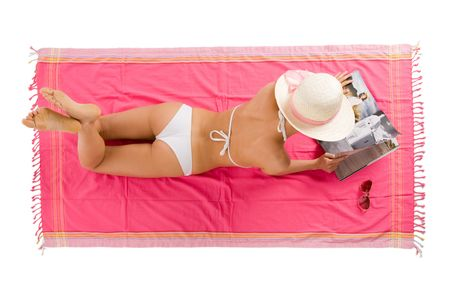Beautiful girl tanning lying on the beach towel. Stock Photo