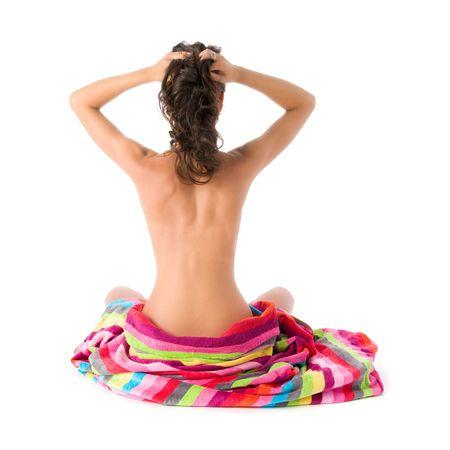 Girl sitting with towel and hands between the hair, image taken from behind Stock Photo