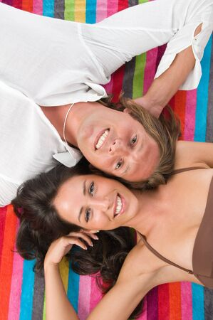 Couple lying on the coloured  beach towel. Picture taken from above photo