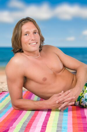 Handsome man lying on the beach Stock Photo