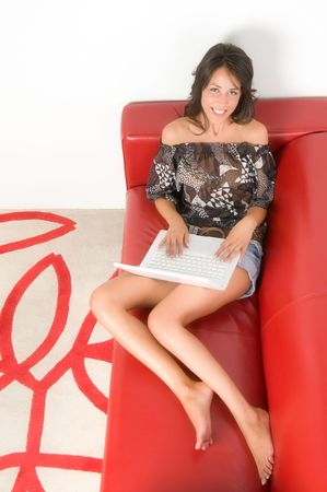 Full length of a young woman lying on the sofa using laptop. Picture taken from above photo