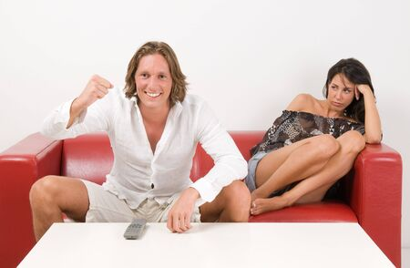 Girl sad because her boyfriend watching soccer play on tv. Domestic life