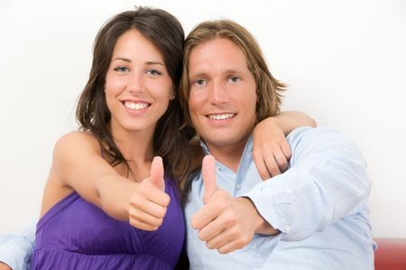 Young couple embraced on the sofa with thumbs up photo
