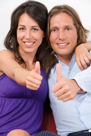 Young couple embraced on the sofa with thumbs up sign photo