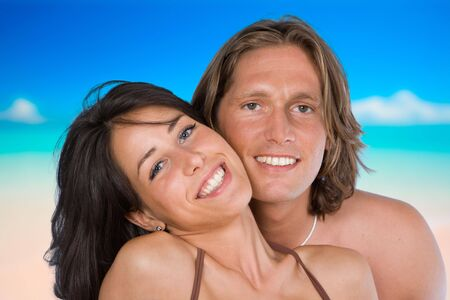 An attractive couple looking at the camera on the beach