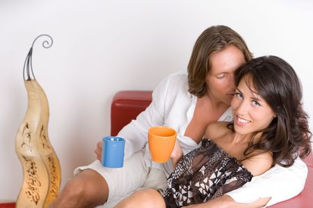 Young couple in love sitting on the couch drinking Stock Photo - 3646376
