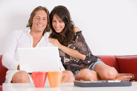 young couple on the sofa play with the notebook Stock Photo