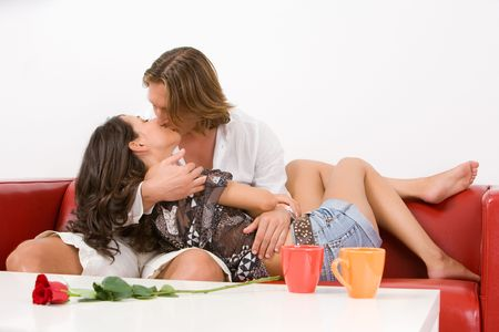 Young happy couple kissing passionately on the sofa