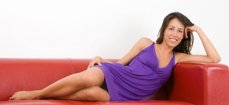 Charming girl wearing a purple dress and she is lying on a red leather sofa photo