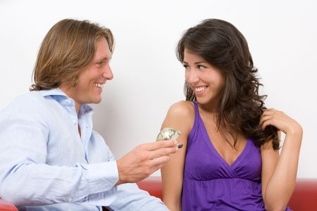 Young couple sitting on the sofa with engagement ring photo