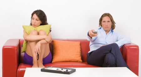 Portrait of a young bored couple sitting on the sofa in their home
