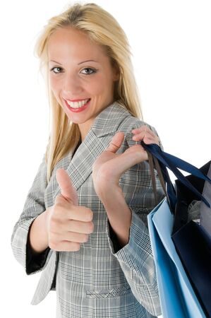 Lovely young blond smiling woman with shopping bags and thumbs up over white photo
