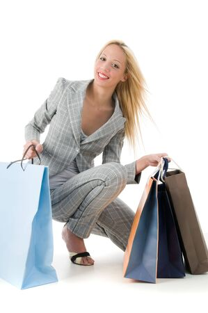 Lovely young blond smiling woman with shopping bags over white
