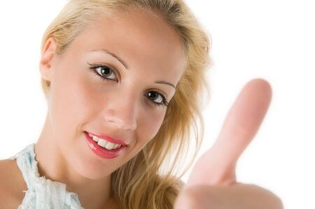 Closeup of a smiling young woman showing thumbs up sign over white background photo