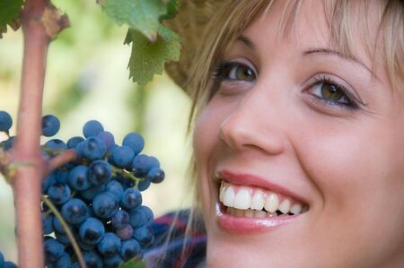 Smiling young woman near bunch of grapes