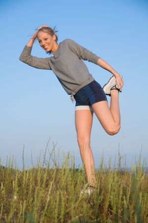 Athletics young woman stretching in a hilly meadow Stock Photo - 3646409