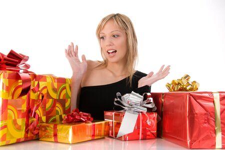 Beautiful blonde girl looks many colorful gifts. Isolated image on white background photo
