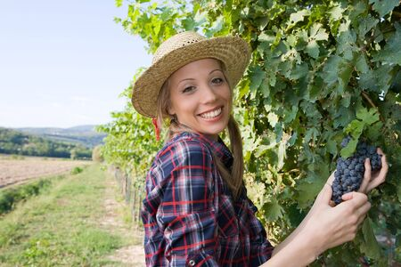 Closeup portrait of a happy young peasant woman among the vineyards photo