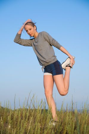 Athletics young woman stretching in a hilly meadow Stock Photo - 3654828