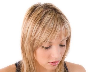 Beautiful blond  girl looks down with toughtful glance. Isolated image with white background photo