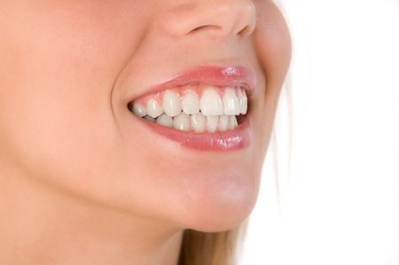Closeup of beautiful smile of young woman. Isolated over white background