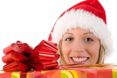 Blonde smiling girl with Santas hat look at the camera between the gift. Isolated image on white background photo