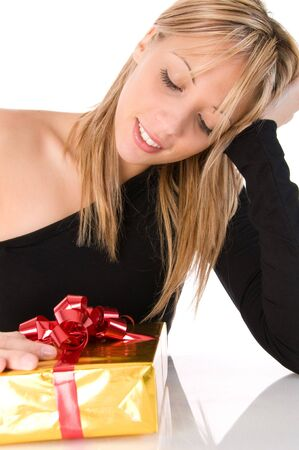 Young beautiful woman looks at the gift withthoughtful expression. Isolated image on the white background photo