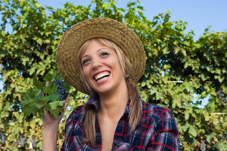 Closeup portrait of a happy young peasant woman among the vineyards