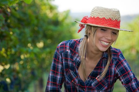 Young peasant woman having fun among the vineyards during the harvest photo