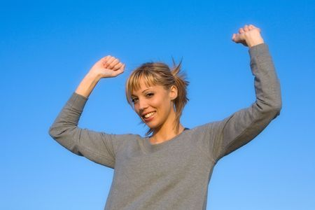 Young smiling woman spreading arms to  blue sky photo