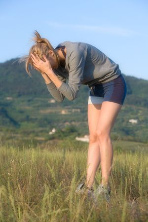 Young woman after sports in a hilly meadow photo