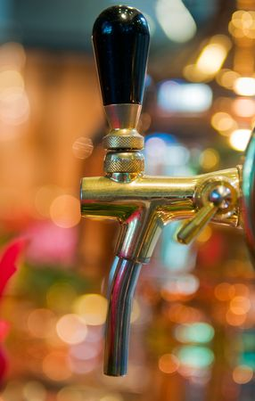 Close up of golden beer tap with blurred background Stock Photo