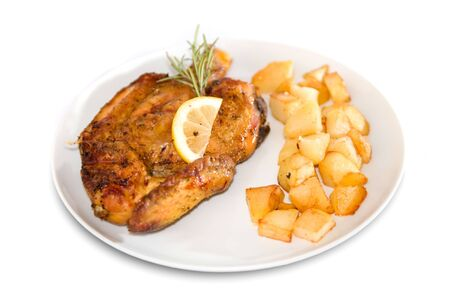 Roasted chicken with baby roast potatoes decorated with rosemary and lemon slices Stock Photo