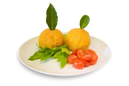 Rice meatballs decorated with cherry tomatoes, celery and bay laurel Stock Photo