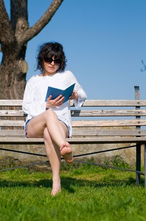 Beautiful caucasian college student sitting on garden seat on campus Stock Photo