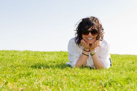 Smiling young woman lying on the grass with blue sky wears big sunglasses