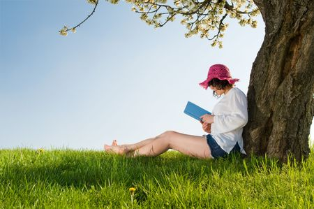 Young woman sitting under a blossom tree reads a book while wearing a lovely purple hat