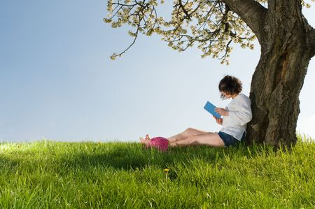 Young woman sitting under a blossom tree reads a book in a beautiful sunny day