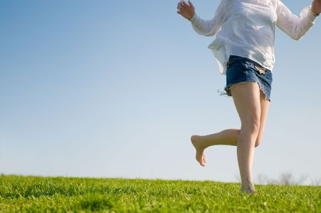 Barefoot girl runs on a green lawn wearing miniskirt and white jersey in a beautiful sunny day