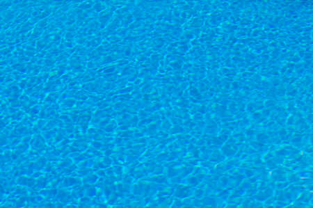 Clear water in the swimming pool. Background texture